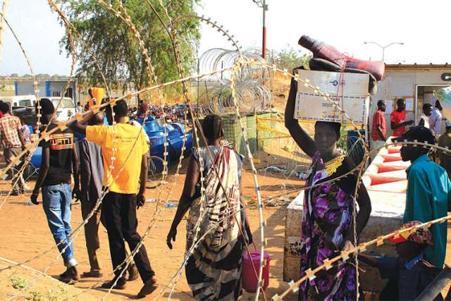 People walk past razor wire at Tomping camp, where thousands of displaced people who fled their homes are sheltered by the United Nations near Juba, South Sudan.