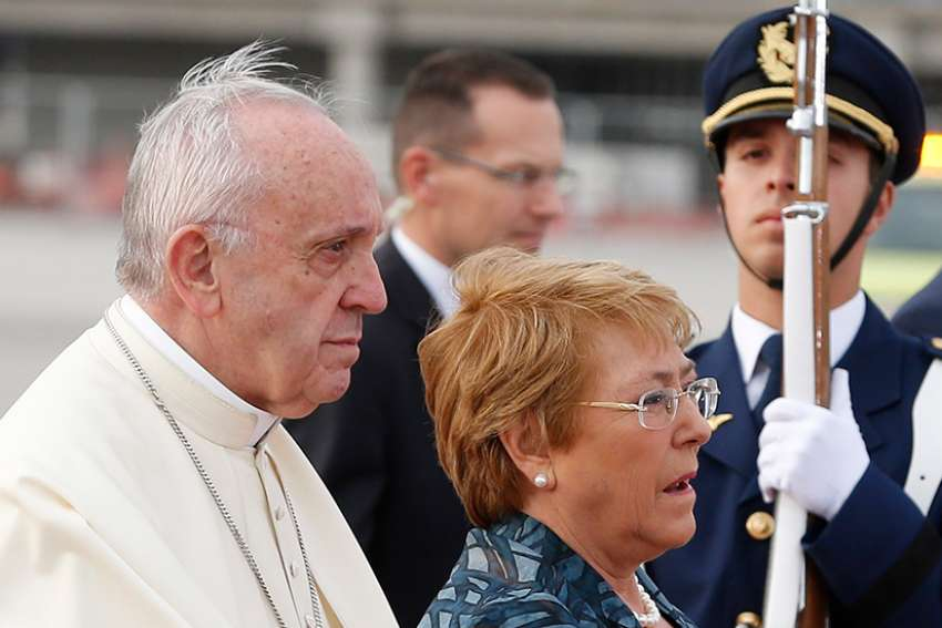 Pope Francis walks with Chilean President Michelle Bachelet as he arrives at the international airport in Santiago, Chile, Jan. 15.