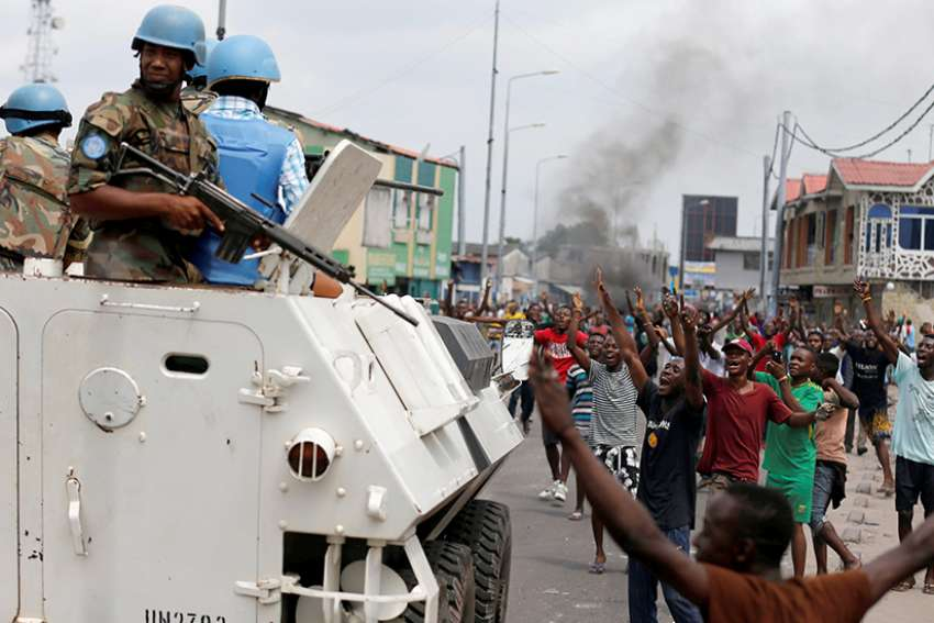 People chant slogans against Congolese President Joseph Kabila as armed U.N peacekeepers watch protesters Dec. 20, 2016 in Kinshasa.  In the Democratic Republic of the Congo, political unrest first erupted in 2015 after a bill was proposed which would potentially delay the presidential and parliamentary elections. The bill was widely seen by the opposition as a power grab on the part of Kabila.