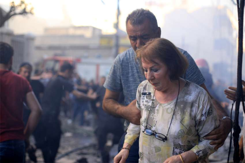 A woman is assisted at the site of a car bomb blast outside the Syriac Orthodox Church of the Blessed Virgin Mary in Qamishli, Syria, July 11, 2019. At least 11 people were injured in the blast during evening services. It was unclear who was responsible for the attack.