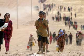 Children flee violence from forces loyal to the Islamic State in Sinjar, Iraq. Cardinal Fernando Filoni said international action is necessary to guarantee the possibility of survival in Iraq.