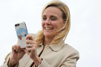 A woman with a smartphone cover featuring Pope Francis takes pictures as people await his on the airfield at Joint Base Andrews in Maryland Sept. 22, 2015.
