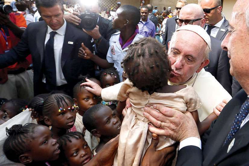 Pope Francis kisses a child as he visits a refugee camp in Bangui, Central African Republic, Nov. 29