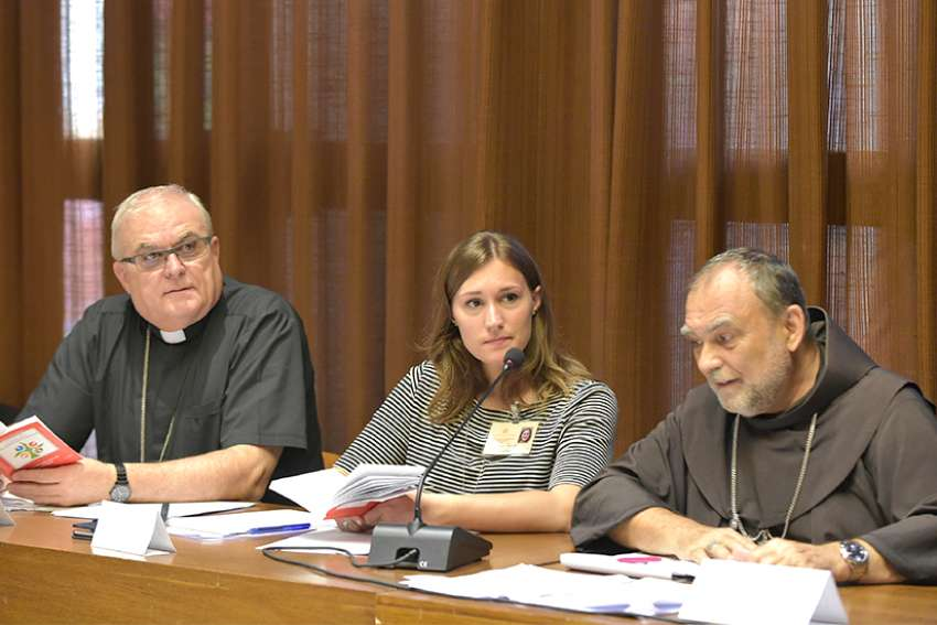 Emilie Callan, center, a synod delegate from Canada, attends a working group at the Synod of Bishops on young people, the faith and vocational discernment at the Vatican Oct. 10.