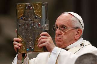 Pope Francis raises the Book of the Gospels as he celebrates Holy Thursday chrism Mass in St. Peter's Basilica at the Vatican April 13.