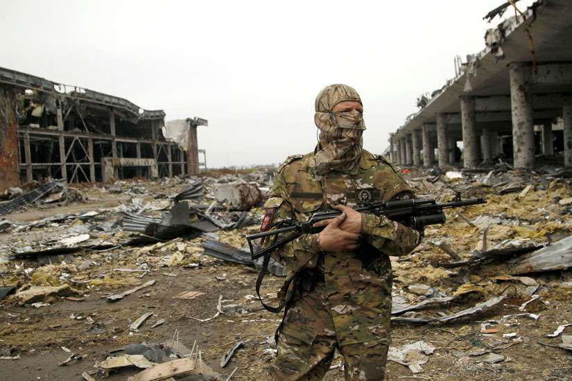A member of the self-proclaimed Donetsk People's Republic forces stands guard near buildings destroyed during battles with Ukrainian armed forces, at Donetsk airport, Ukraine, June 1. Pope Francis has established a committee to distribute aid in Ukraine with an ecumenical, interreligious approach.