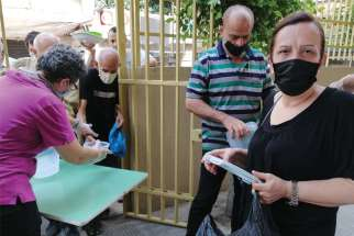 At the Socio-Medical Intercommunity Dispensary in the Naba neighbourhood of Beirut, people receive a hot meal to take back to their homes Sept. 2. The centre experienced considerable damage from the explosion in Beirut's port area Aug. 4.