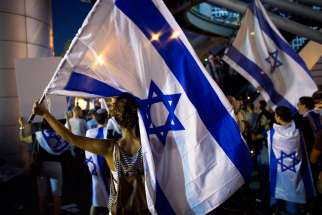 Activists hold flags in Tel Aviv, Israel, July 29 to show support for Israel's offensive in the Gaza Strip. Tour operators interview by Catholic News Service say the ongoing violence in Middle East has not affected pilgrimages to the Holy Land.