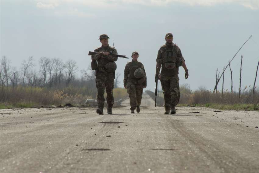 Service members of the Ukrainian armed forces walk along a road near the line of separation outside the rebel-controlled city of Donetsk April 26, 2021.