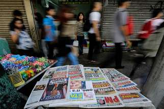 "In this 2016 file photo, Filipinos walk past a newspaper stand in Manila, Philippines. A Philippine church official urged about 150 priests, women religious and lay people working in Catholic media to confront ""fake news"" during the annual National Catholic Media Convention Aug. 6-9 in Davao City."
