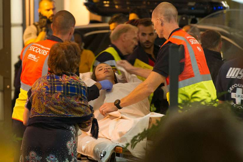 Paramedics rush a young woman to a waiting ambulance July 14 as they evacuate victims from the scene where a truck crashed into the crowd during the Bastille Day celebrations in Nice, France. More than 80 people were killed and the death toll was rising.