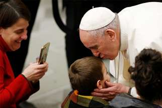 Pope Francis greets a boy as he meets the sick and disabled during his general audience in Paul VI hall at the Vatican Feb. 20, 2019.
