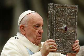 "Pope Francis holds the Book of the Gospels as he celebrates Mass on the feast of Mary, Mother of God, in St. Peter's Basilica at the Vatican Jan. 1, 2020. The pope has established the third Sunday in Ordinary Time as ""Sunday of the Word of God."" It will be celebrated for the first time Jan. 26."