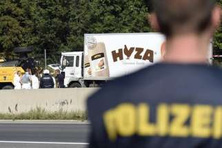 Forensic experts investigate a truck in which refugees were found dead on a freeway between Parndorf and Neusiedl, Austria, Aug. 27.