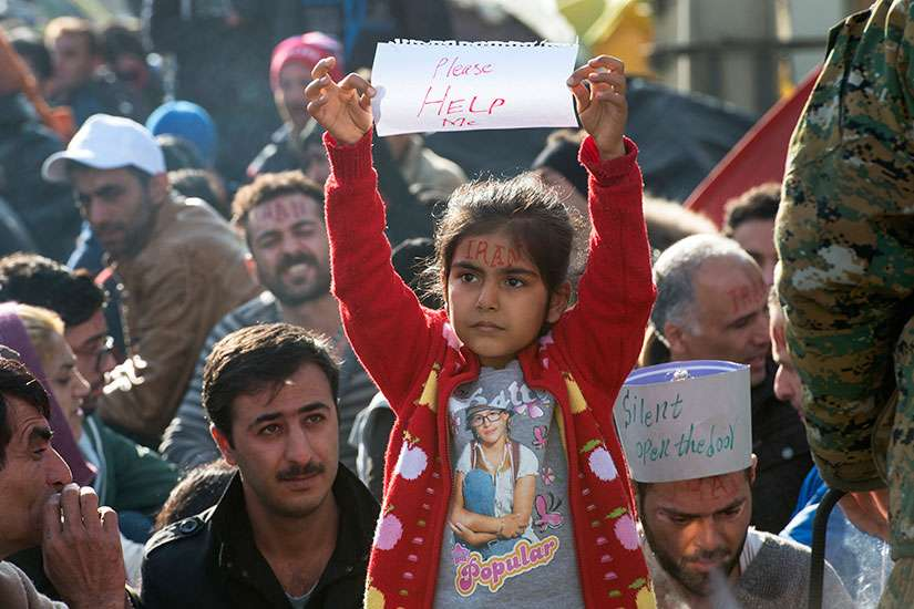An Iranian girl raises a sheet of paper with 'Please HELP Me' on it Nov. 24 as a group of people wait for permission to cross the border from Greece into Macedonia. Macedonia began granting entry only to refugees from Syria, Iraq and Afghanistan.