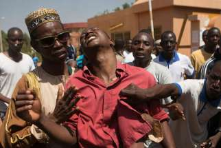 "An anti-government protester is helped after being shot in Ouagadougou, Burkina Faso, Oct. 30. Burkina Faso's Catholic bishops sent a ""message of peace and hope"" to the West African country after its 27-year president, Blaise Compaore, fled prompting a m ilitary takeover."